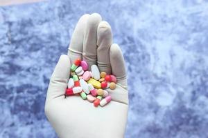 mão segurando um monte de pílulas coloridas