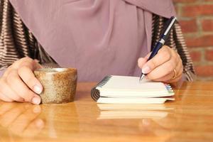 perto da mão de uma mulher escrevendo no bloco de notas