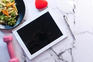 tablet digital em bancada de mármore com halteres e salada