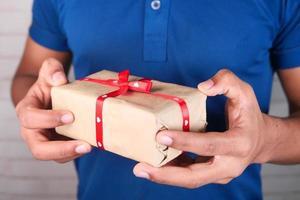 homem segurando um presente de dia dos namorados foto