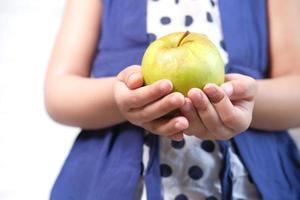 criança segurando maçã verde