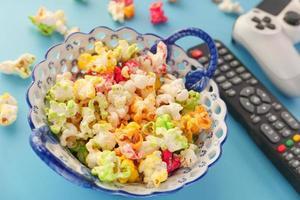 close up de pipoca colorida e controle remoto de tv na mesa