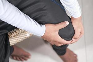 homem segurando o joelho com dor