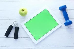 tablet digital com equipamentos esportivos em fundo preto foto