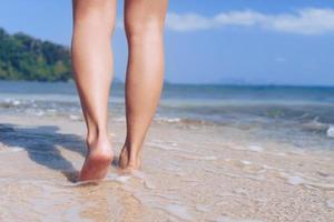 pés de mulher caminhando lentamente na praia tropical de areia foto