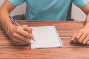 pessoa escrevendo um livro em uma mesa foto