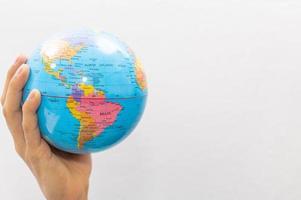 mão segurando um pequeno globo terrestre no fundo branco foto