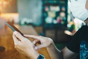 homem usando uma máscara usando um smartphone em um café público