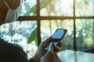 homem usando máscara usando um smartphone em um café público