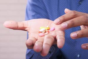 close-up de homem segurando comprimidos e cápsulas