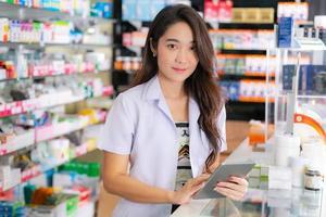 farmacêutica asiática usa tablet digital na farmácia