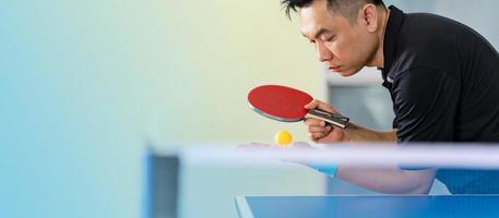 masculino jogando tênis de mesa com raquete e bola em um ginásio esportivo