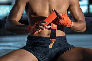 lutador amarrando fita adesiva antes da luta, boxe tailandês foto