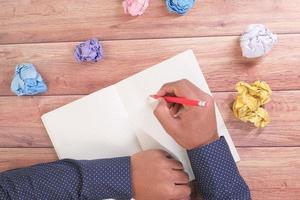 homem escrevendo em um diário com papel amassado