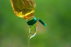 óleo vegetal derramando da garrafa com fundo natural