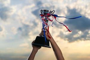 um homem segurando uma taça de troféu contra o fundo do céu nublado do crepúsculo