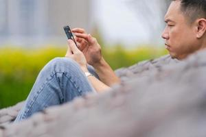 homem relaxando e usando smartphone no parque da cidade