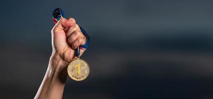 mão segurando a medalha de ouro contra o fundo do céu nublado do crepúsculo