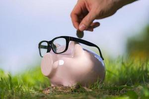 cofrinho rosa com óculos na grama e mão colocando uma moeda