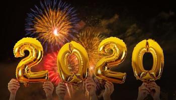 mãos segurando balões com o número 2020 com fundo de fogos de artifício
