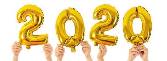 mãos segurando balões com números de 2020 em fundo branco