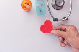 segurando um coração vermelho com suprimentos médicos