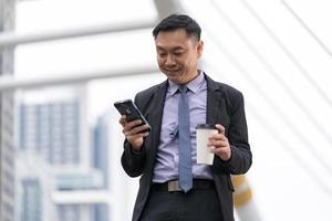 empresário asiático em pé e segurando um telefone celular com prédios de escritórios comerciais ao fundo da cidade