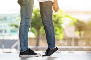casal se beijando, garota fica na ponta dos pés para beijar o homem foto