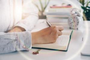 mulher escrevendo no caderno de planejamento enquanto usa o laptop para trabalhar