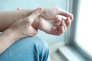 mãos de uma jovem com dor no pulso