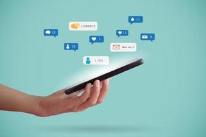 mão segurando um smartphone com ícones de comunicação
