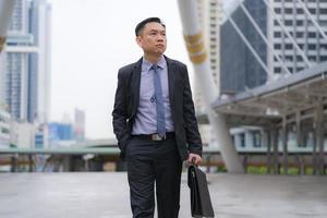 empresário asiático andando e segurando uma pasta com prédios de escritórios comerciais ao fundo da cidade