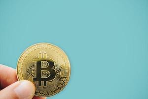 mão segurando um símbolo de bitcoins como criptomoeda de dinheiro digital foto