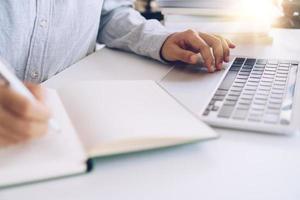 mulher escrevendo em um caderno de planejamento enquanto usa o laptop em casa