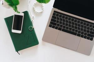 vista superior de um laptop moderno ou notebook com telefone para o trabalho foto