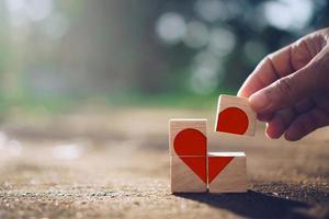 mão segurando um cubo de madeira com o ícone do sinal de coração e a luz do sol da natureza