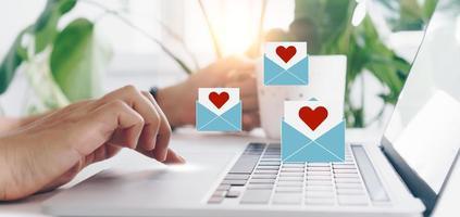 mão digitando teclado com laptop com mídia social carta de amor enviar ícones do dia dos namorados.