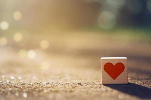 cubo de madeira com ícone de sinal de coração e copie o espaço com luz solar natural