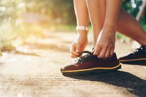 mulher usando tênis de corrida e correndo em fundo verde natural