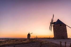 velhos moinhos de vento ao pôr do sol
