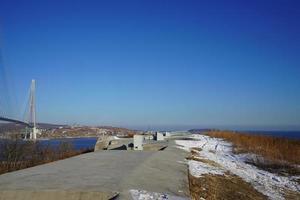 bateria voroshilovskaya e ponte russky contra um céu azul claro em vladivostok, Rússia foto