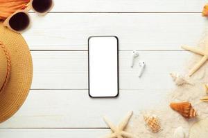 vista superior de uma maquete de smartphone com itens de verão foto
