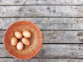 ovos marrons em uma cesta de vime no fundo da mesa de madeira