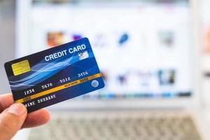 mãos segurando um cartão de crédito e usando um laptop, conceito de compras online foto