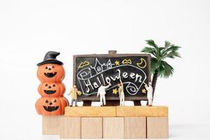 pessoas em miniatura colorindo decorações de adereços de festa de halloween em um fundo branco, conceito de festa de halloween