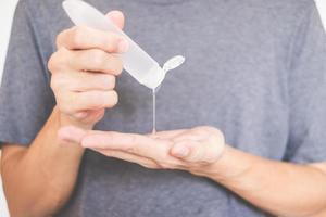 mãos de homem usando dispensador de gel desinfetante para as mãos contra o novo coronavírus ou covid-19, conceito de higiene e saúde