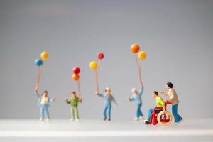 pessoas em miniatura mostram uma família positiva cuidando de seu pai deficiente foto
