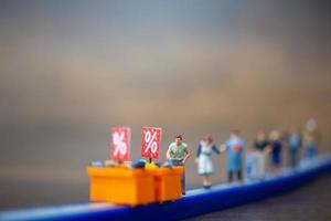 pessoas em miniatura mantendo distância, compras, conceito de distanciamento social foto