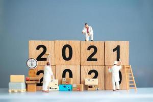 trabalhadores em miniatura pintando 2021 e removendo números de 2020, conceito de feliz ano novo foto