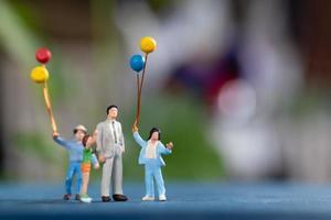 família feliz em miniatura segurando balões em um fundo desfocado